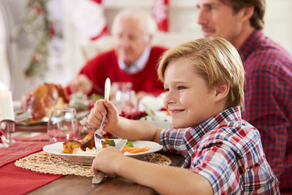 Son With Father And Grandparents Enjoying Christmas Meal