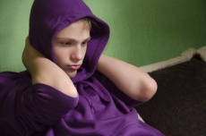 Depressed teenager with arms around his neck and hood on head