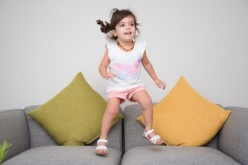Joyful girl dancing and jumping on sofa